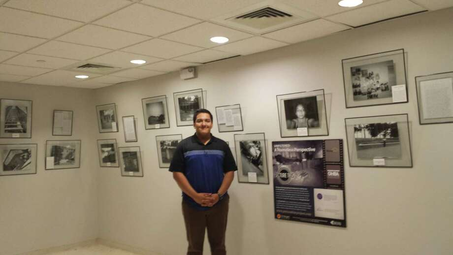 Javier Perea, HomeAid Houston intern, helps install Picture This Homeless Youth exhibit at City Hall. It will be on display until July 3.