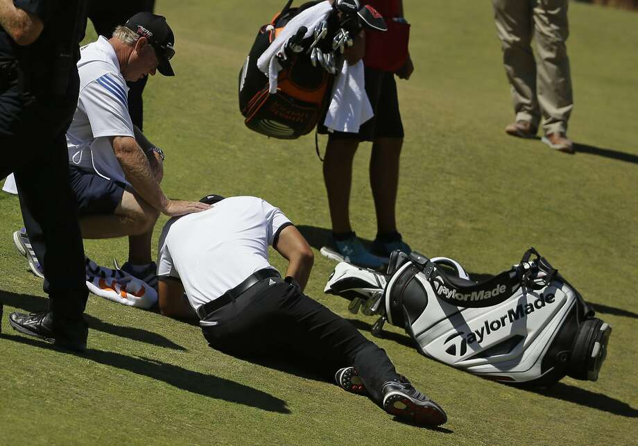 Jason Day of Australia lies in the fairway after falling down as his caddie Colin Swatton crouches beside him on the ninth hole during the second round. Photo: Ted S. Warren, Associated Press