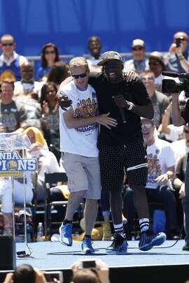 Golden State Warriors' Draymond Green, right, brings head coach Steve Kerr back on stage as they spoke during the NBA Champions rally at the Henry J. Kaiser Convention Center on Friday, June 19, 2015 in Oakland, Calif.