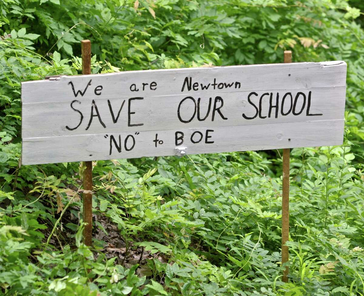 One of the signs by Aaron Cox's driveway opposes the closure of Hawley Elementary School in Newtown.