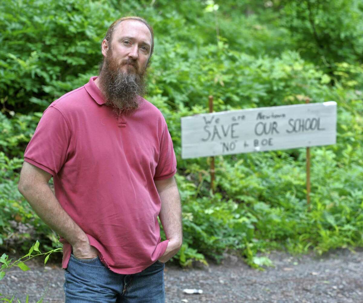 Aaron Cox stands at the end of the driveway to his Newtown home where he has put up signs requesting Hawley Elementary School not be closed.