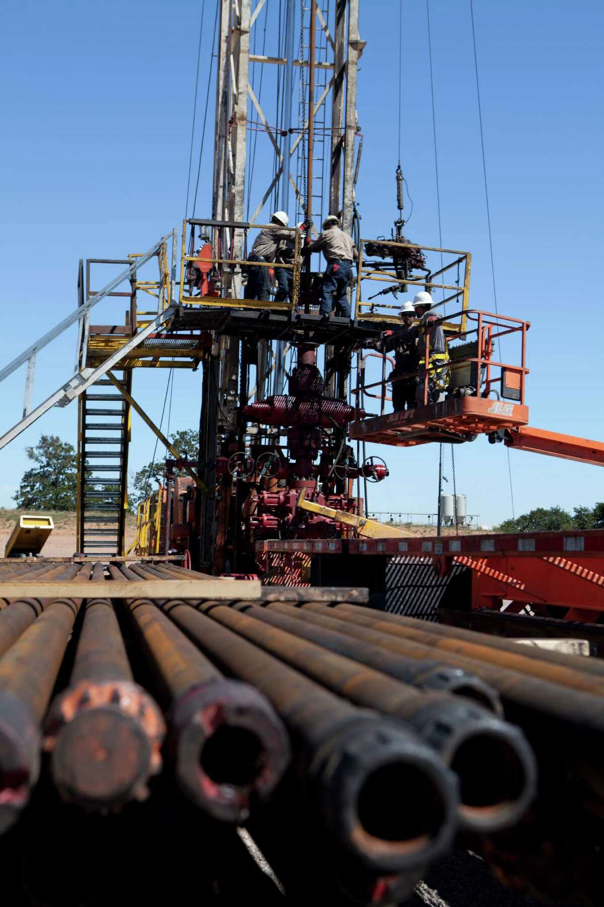 In this 2013 file photo, a drill crew adds new sections of pipe to a string as they drill deeper into a Newfield Exploration well. As the well is drilled, it is lined with steel casing to prevent the hole from collapsing and fluids and gas from escaping. Central Oklahoma, Newfield Exploration Company, Workover rig, Basin Energy, Casados 4 H 21X Well, Stephens County, OK. 2.75 inch pipe. Workover rig is the workhorse, as it keeps working before and after the well is drilled. Preparing a well for production. Performing a variety of functions to enhance well performance.