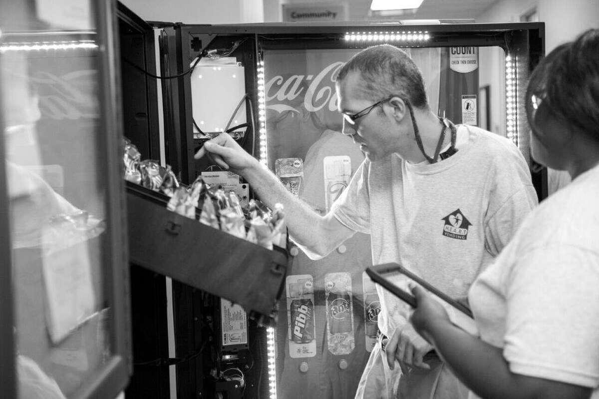 Bradley Borochoff loads a H.E.A.R.T. vending machine.
