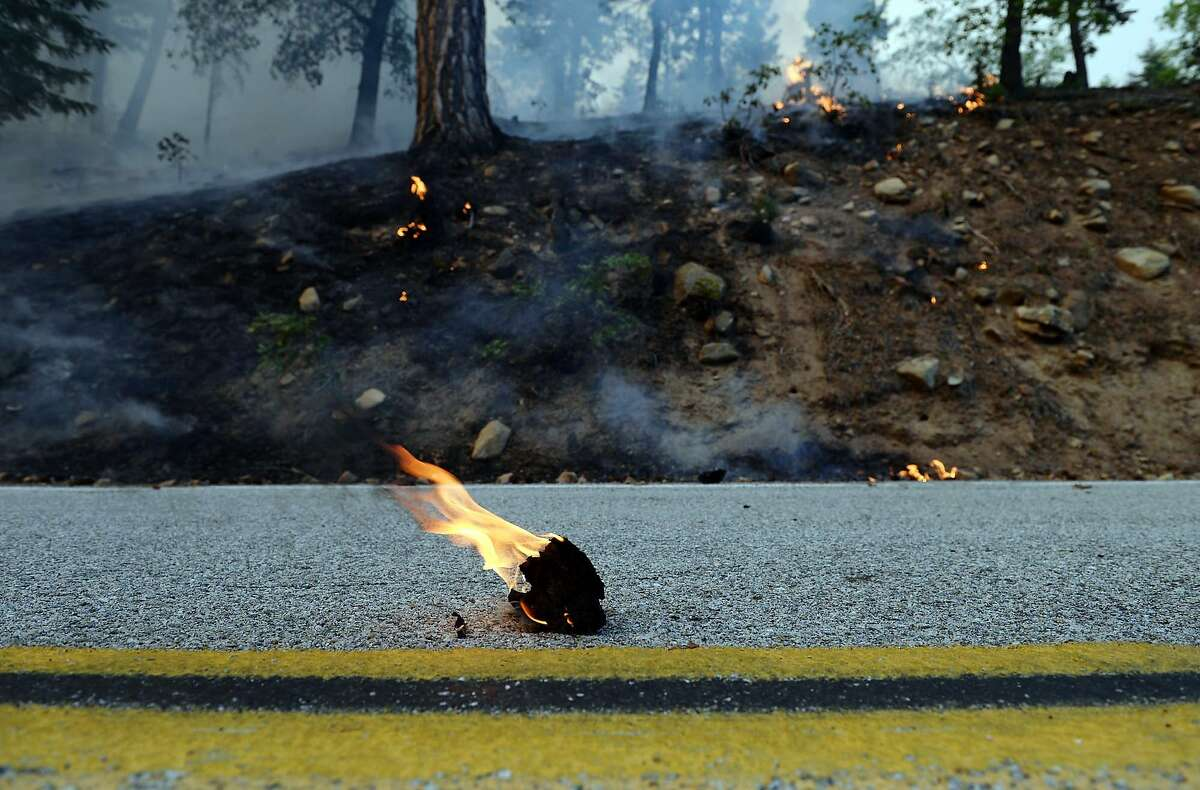 Debris burns on Jenks Lake Road as the Lake Fire burns for a second day on Thursday, June 18, 2015, in Angeles Oaks, Calif. Firefighters battled two blazes in Southern California, one that was growing as it churned through 30-foot pine trees in a remote area of the San Bernardino Mountains and another that was slowing in northern San Diego County. (Micah Escamilla/The Sun via AP) MANDATORY CREDIT
