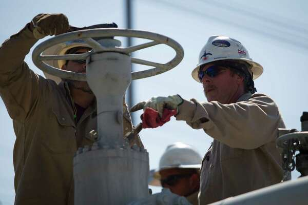 Mark Manuel and Rick Kimbro, provide maintenance to pipeline valves in Webster, Tuesday, June 2, 2015.