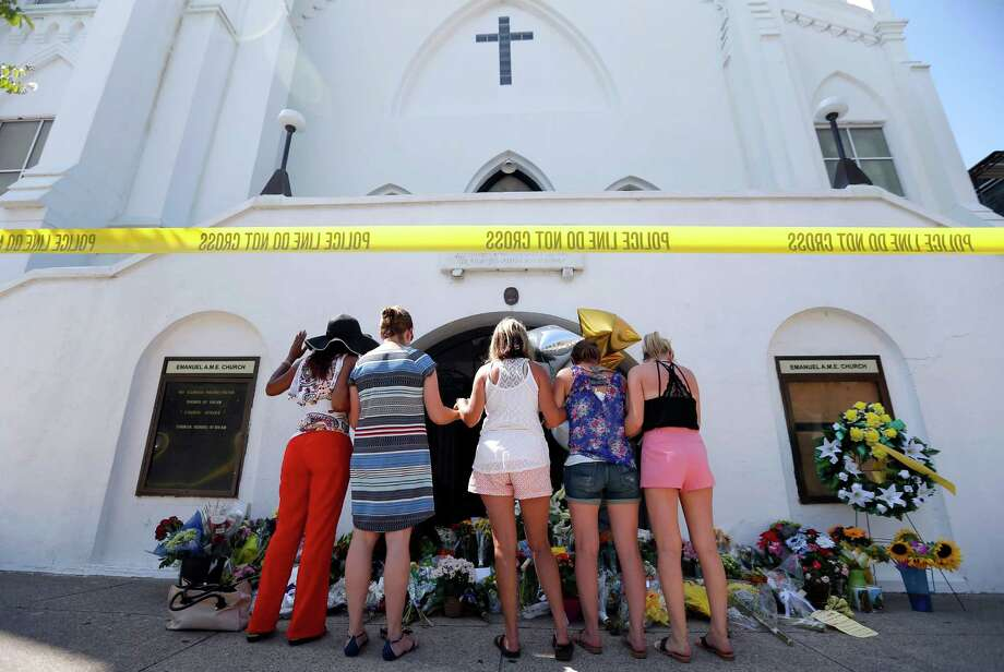 A group of women prays together at a makeshift memorial on the sidewalk in front of the Emanuel AME Church in Charleston, S.C. Photo: Stephen B. Morton, FRE / FR56856 AP