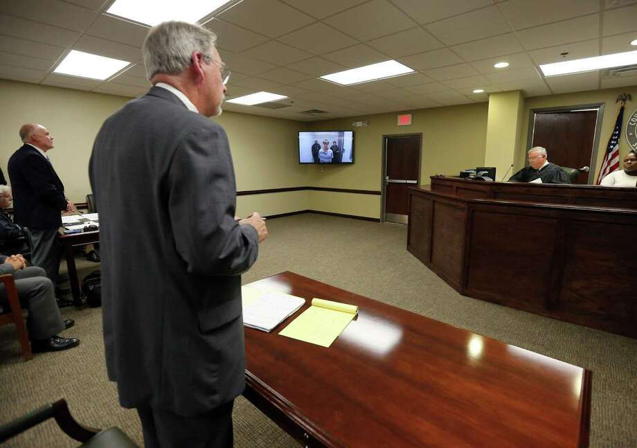 CORRECTS SPELLING OF DYLANN NOT DYLAN - Charleston Police Detective Richard Burckhardt, background left, addresses Judge James Gosnell during a bond hearing for Dylann Storm Roof at a court in North Charleston, S.C. on Friday, June 19, 2015. Ninth Circut Public Defender Ashley Pennington is in the foreground. Roof, 21, who faces nine counts of murder in the shooting deaths at the Emanuel African Methodist Episcopal Church, appeared by video from the county jail. (Grace Beahm/The Post and Courier via AP, Pool) Photo: Grace Beahm, POOL / Associated Press / POOL The Post and Courier