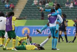 Cameroon's goalkeeper Annette Ngo Ndom (1) jumps into the arms of a teammate after defeating Switzerland in a FIFA Women's World Cup soccer match, Tuesday, June 16, 2015 in Edmonton, Alberta, Canada. (Jason Franson/The Canadian Press via AP) MANDATORY CREDIT