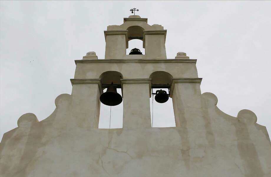 A mockingbird sits atop the chapel at Mission San Juan Capistrano on June 19. Officials held a ceremony at the mission to mark the expansion of lands around the San Antonio Photo: Kin Man Hui /San Antonio Express-News / ©2015 San Antonio Express-News