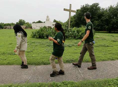 "Members of the Texas Conservation Corps of Americorps walk along the grounds of Mission San Juan Capistrano after a ceremony to mark the expansion of lands around the San Antonio Missions in order to preserve the land and environment on Friday, June 19, 2015. ""The San Antonio Missions Historical Park protects our nation's largest collection of Spanish colonial resources, and today we extend that protection even further, enhancing the experience of visitors to the Missions and vastly expanding the park's economic impact on the city of San Antonio,"" said Suzanne Dixon of the National Parks Conservation Association in a press release. The San Antonio River Authority and the City of San Antonio will transfer about 60.5 acres of land around Mission San Juan to the National Park Service as part of the preservation efforts. (Kin Man Hui/San Antonio Express-News) Photo: Kin Man Hui, Staff / San Antonio Express-News / ©2015 San Antonio Express-News"