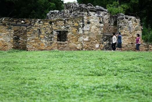 "Visitors walk along the ground of Mission San Juan Capistrano after a ceremony to mark the expansion of lands around the San Antonio Missions in order to preserve the land and environment on Friday, June 19, 2015. ""The San Antonio Missions Historical Park protects our nation's largest collection of Spanish colonial resources, and today we extend that protection even further, enhancing the experience of visitors to the Missions and vastly expanding the park's economic impact on the city of San Antonio,"" said Suzanne Dixon of the National Parks Conservation Association in a press release. The San Antonio River Authority and the City of San Antonio will transfer about 60.5 acres of land around Mission San Juan to the National Park Service as part of the preservation efforts. (Kin Man Hui/San Antonio Express-News) Photo: Kin Man Hui, Staff / San Antonio Express-News / ©2015 San Antonio Express-News"