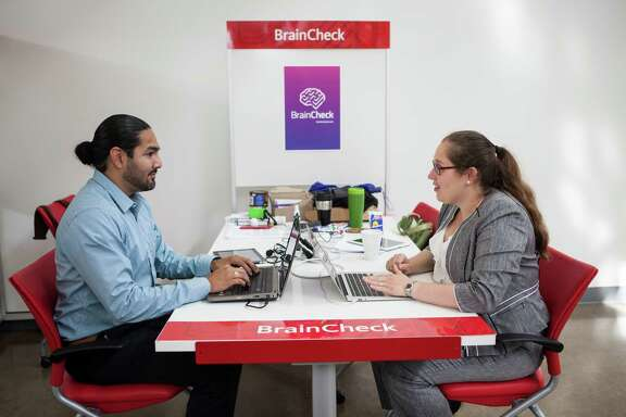 Yael Katz, right , the CEO of BrainCheck and Benjamin Flores, left, work at their station in the TMCX offices in Houston, TX on Thursday, May 28, 2015.