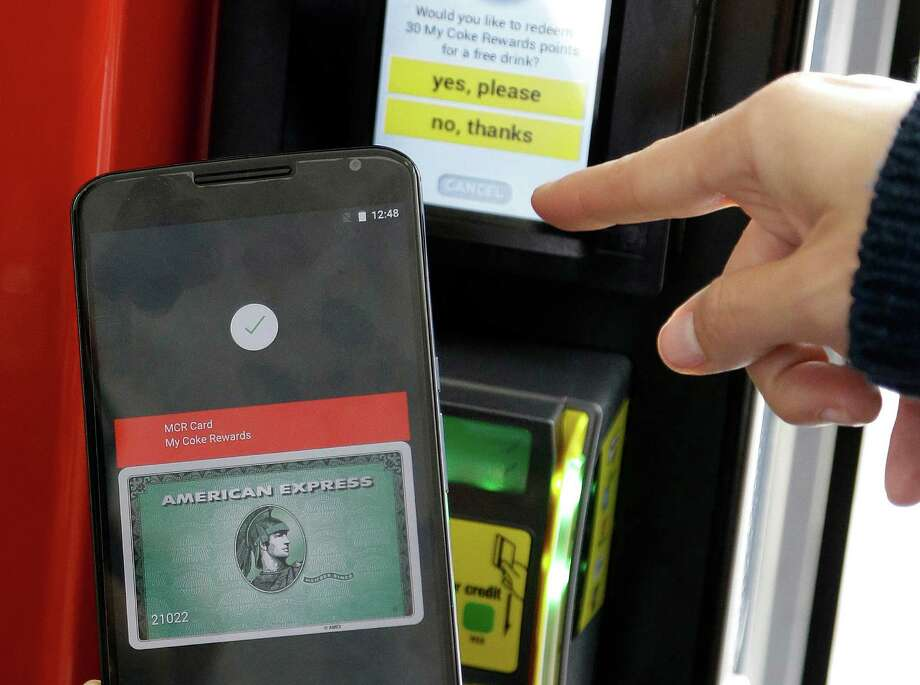 FILE - In this May 28, 2015 file photo, a Google employee gives a demonstration of Android Pay on a phone at Google I/O 2015 in San Francisco. Google's next version of its Android operating system will boast new ways to fetch information, pay merchants and protect privacy on mobile devices as the Internet company duels with Apple in the quest to make their technology indispensable. (AP Photo/Jeff Chiu, File) ORG XMIT: NYBZ123 Photo: Jeff Chiu / AP