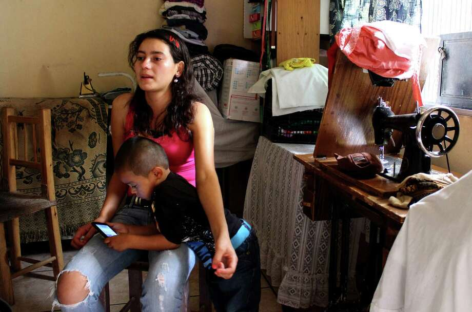 Lilian Oliva Bardales, 19, sits while her son, Christian, 4, plays with her mobile phone in the small living room at a relative's house in a community of Tegucigalpa, Honduras. She was immediately separated from her son after cutting her wrist while in a detention center for migrants in Texas. Photo: Nincy Perdomo, MBR / McClatchy DC
