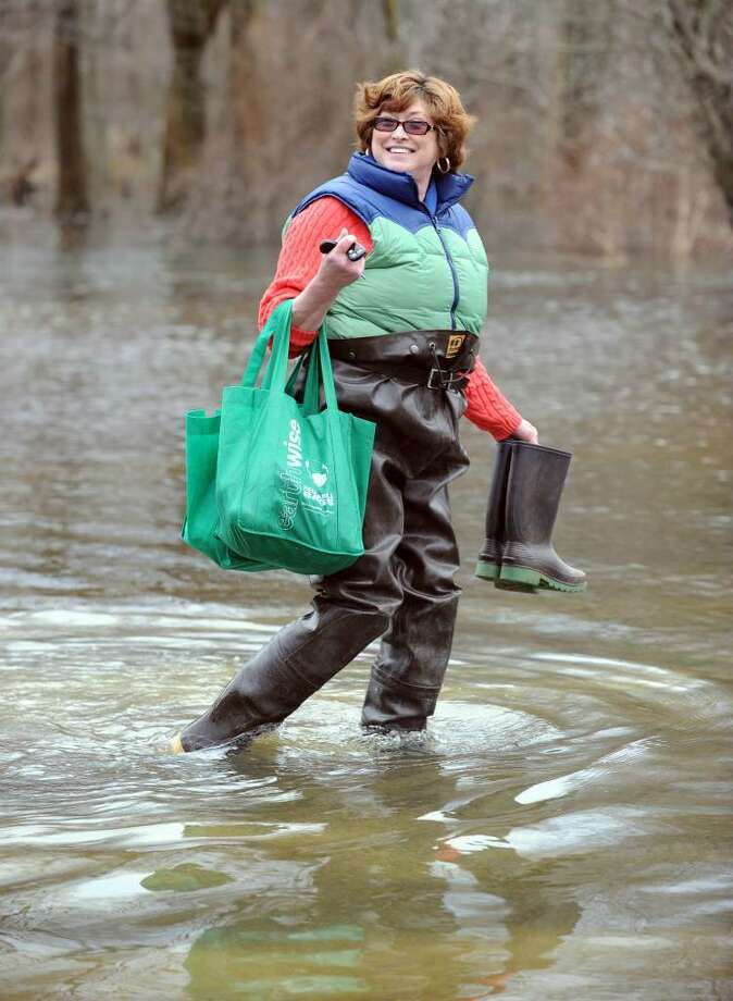 Diane Ragosta, puts on hip boot waders to make her way to her home after grocery shopping Sunday. Ragosta, who lives at Jensen Trailor Park Danbury, parks her car on dry land, puts the boots on and wades to and from her home because of flood waters brought on by recent rains. Photo: Carol Kaliff / The News-Times