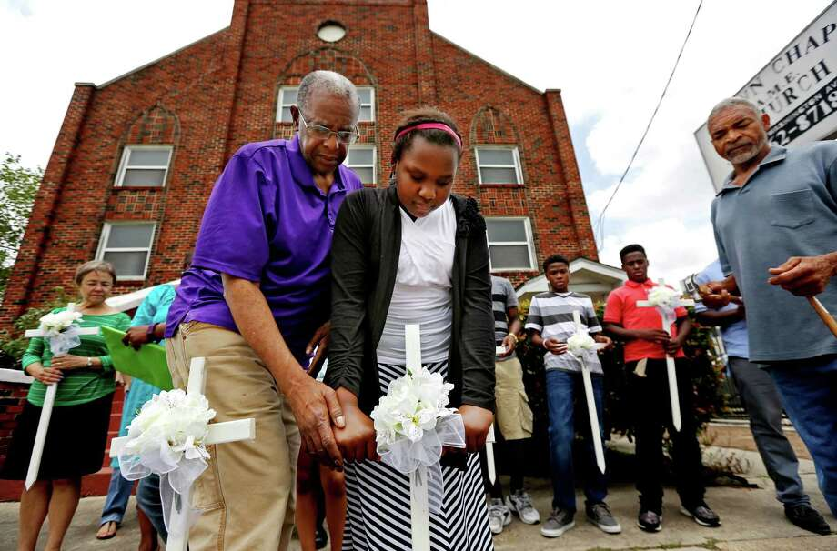 Houstonians, including Kennedy Honors, 12, placed crosses Friday at Brown Chapel African Methodist Church to honor the nine people killed Wednesday in Charleston, S.C. Photo: Gary Coronado, Staff / © 2015 Houston Chronicle
