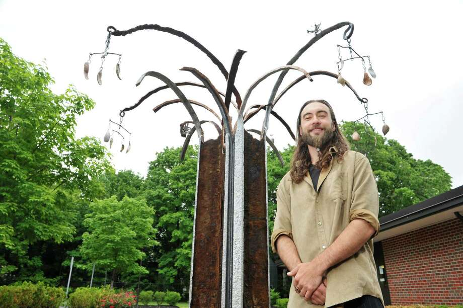 Sculptor Matt Hart poses with his artwork he created outside the Albany Library Delaware Ave. Branch on Tuesday, June 2, 2015, in Albany, N.Y.  The sculpture is made of old trolley rails salvaged when Delaware Avenue was reconstructed.   (Paul Buckowski / Times Union) Photo: PAUL BUCKOWSKI / 00032094A