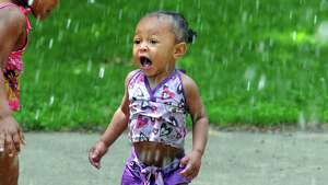 One-year-old Zyana Beasley of Troy excitedly cools down in the spray pad at Frear Park on Friday June 19, 2015 in Troy, N.Y.  (Michael P. Farrell/Times Union)