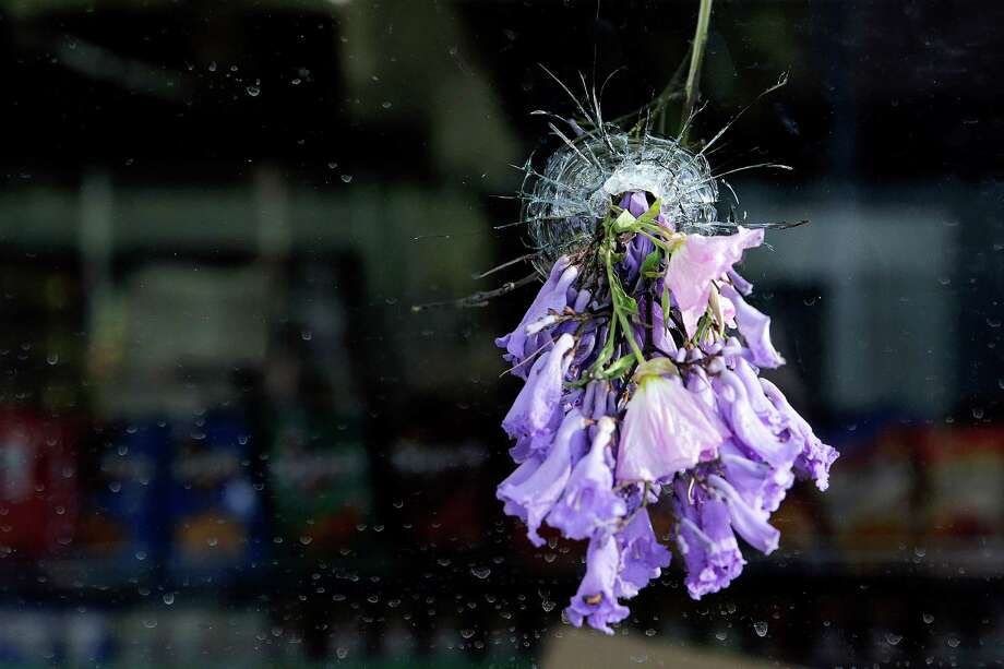 Flowers are placed in a bullet hole on a window of IV Deli Mart, after a mass shooting took place by a drive-by shooter near the UC Santa Barbara campus in 2014. Some of the victims were stabbed and others were shot. Photo: Jae C. Hong / Jae C. Hong / Associated Press 2014 / AP