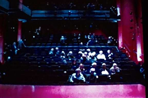 Shot from the audience, looking at the pink-rimmed stage.