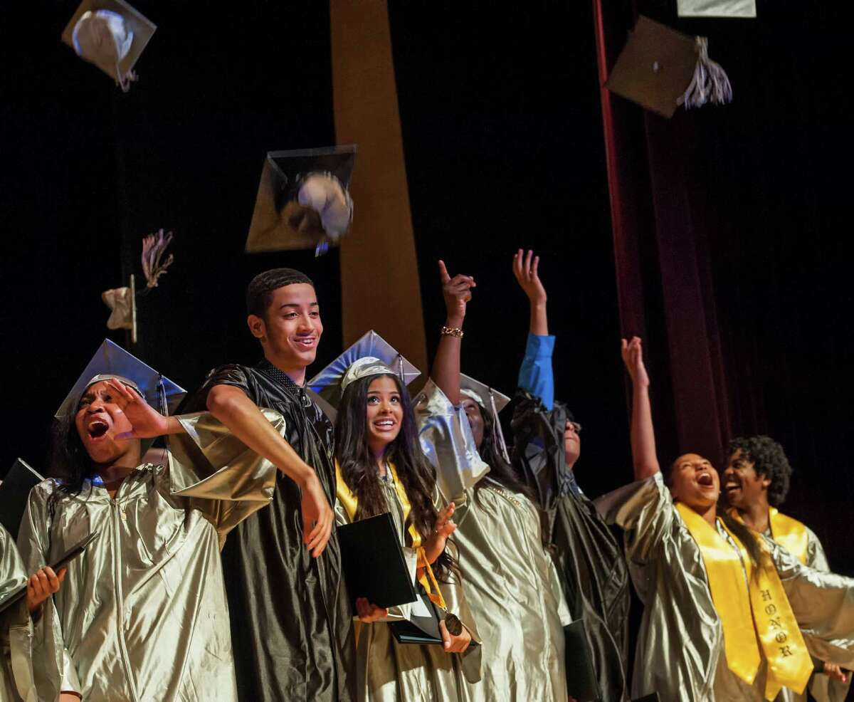 Students from The Bridge Academy toss their caps into the air at the end of the eighteenth annual commencement ceremony held at the Thurgood Marshall Middle School, Bridgeport, CT on Friday, June 19, 2015.