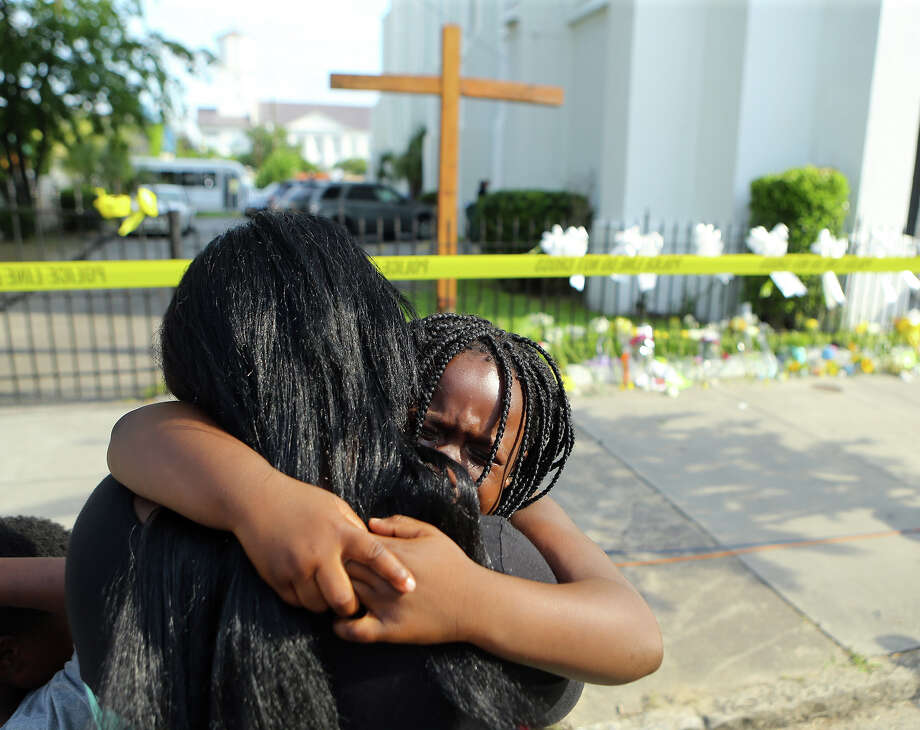 Kearston Farr hugs her 5-year-old daughter Taliyah visiting a memorial in front of the Emanuel AME Church on Friday, June 19, 2015 in Charleston, S.C.  Dylann Storm Roof, 21, is accused of killing nine people during a Wednesday night Bible study at the church.   ( Curtis Compton/Atlanta Journal-Constitution via AP)  MARIETTA DAILY OUT; GWINNETT DAILY POST OUT; LOCAL TELEVISION OUT; WXIA-TV OUT; WGCL-TV OUT    ORG XMIT: GAATJ105 Photo: Curtis Compton / AJC