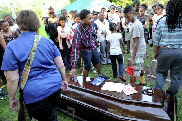 Attendees are invited to leave items on a casket as they say good-bye during a Funeral for Crime and Violence from the African American Burial Ground as part of Juneteenth events on Friday, June 19, 2015, at Vale Cemetery in Schenectady, N.Y. (Cindy Schultz / Times Union) Photo: Cindy Schultz / 00032342A