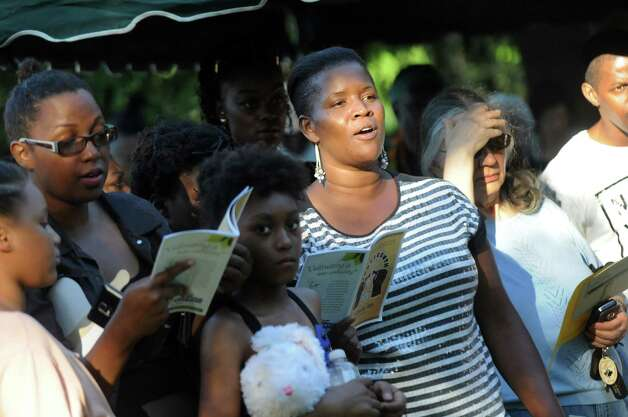 "Ka'Turay Koroma, center, of Schenectady joins others in singing ""Lift Every Voice and Sing"" during a Funeral for Crime and Violence from the African American Burial Ground as part of Juneteenth events on Friday, June 19, 2015, at Vale Cemetery in Schenectady, N.Y. (Cindy Schultz / Times Union) Photo: Cindy Schultz / 00032342A"