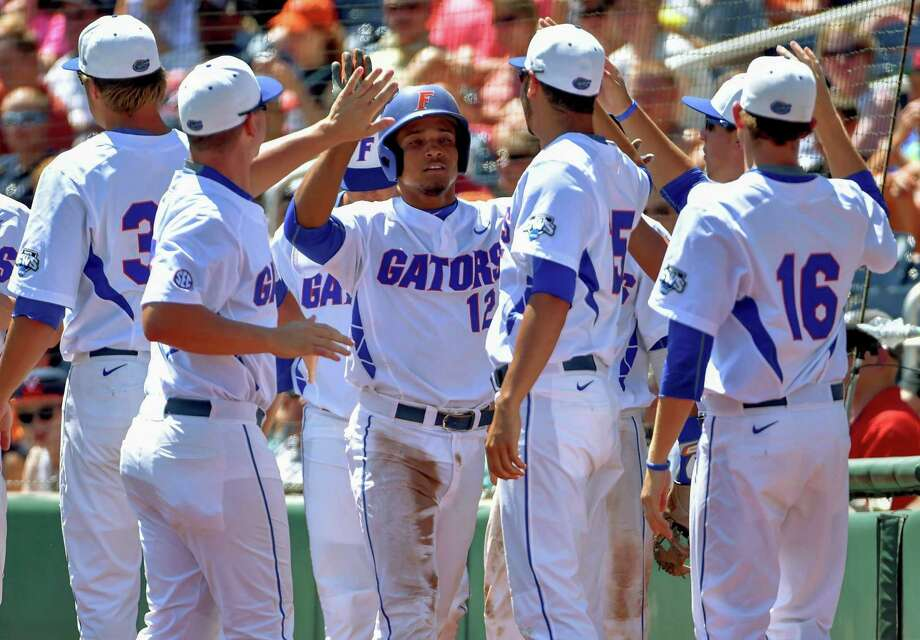 Florida's Richie Martin (12) celebrates his run against Virginia on an RBI single by Josh Tobias in the third inning of an NCAA College World Series baseball game at TD Ameritrade Park in Omaha, Neb., Friday, June 19, 2015. (AP Photo/Mike Theiler) ORG XMIT: NENH107 Photo: Mike Theiler / FR170180 AP