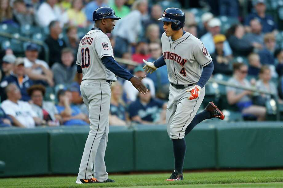 The Astros' George Springer earns a handshake from third-base coach Gary Pettis after Springer homered in the first inning of Friday night's 5-2 loss at Seattle. It was his 11th of the season. Photo: Otto Greule Jr, Stringer / 2015 Getty Images