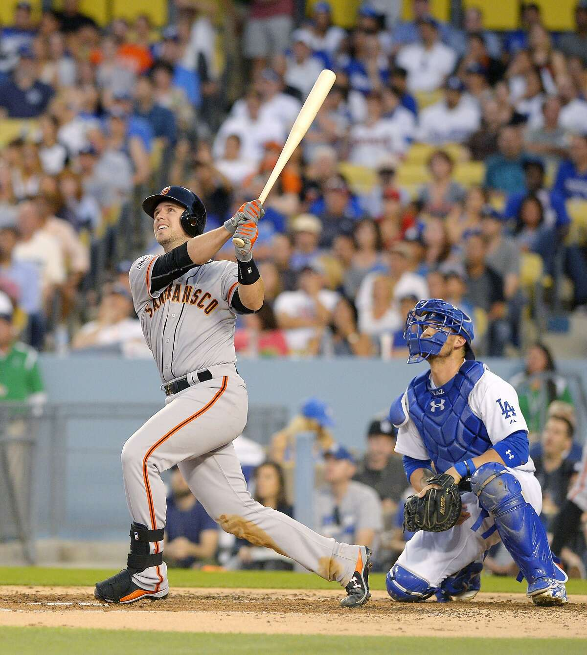 San Francisco Giants' Buster Posey, left, hits a grand slam as Los Angeles Dodgers catcher Yasmani Grandal, watches during the third inning of a baseball game, Friday, June 19, 2015, in Los Angeles.