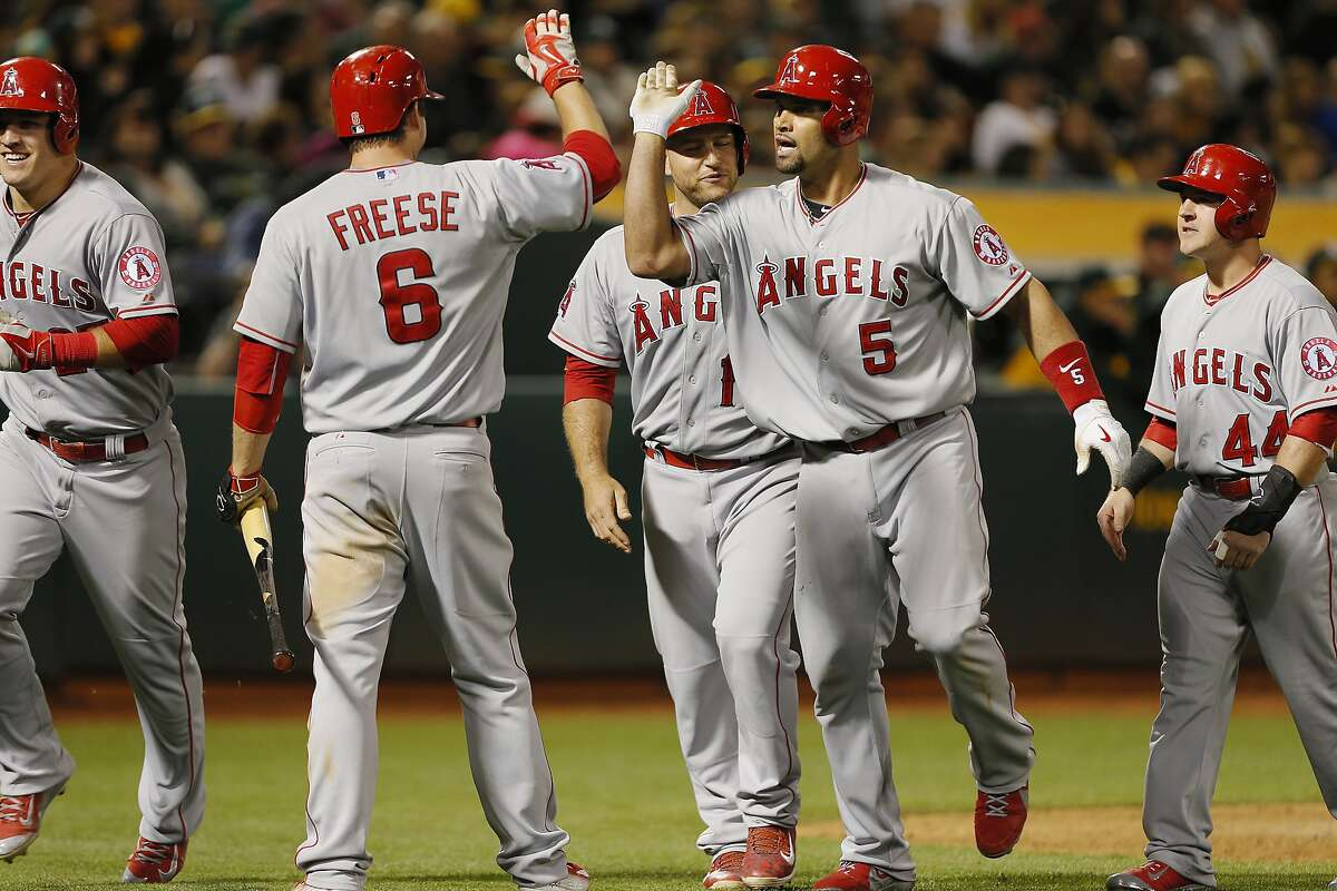 OAKLAND, CA - JUNE 19: Albert Pujols #5 of the Los Angeles Angels of Anaheim celebrates hitting a grand slam with Mike Trout #27, Daniel Robertson #44, and David Freese #6 against the Oakland A's in the seventh inning at O.co Coliseum on June 19, 2015 in Oakland, California. The Angels took the lead with the slam and are ahead 10-7 in the ninth inning. (Photo by Brian Bahr/Getty Images)