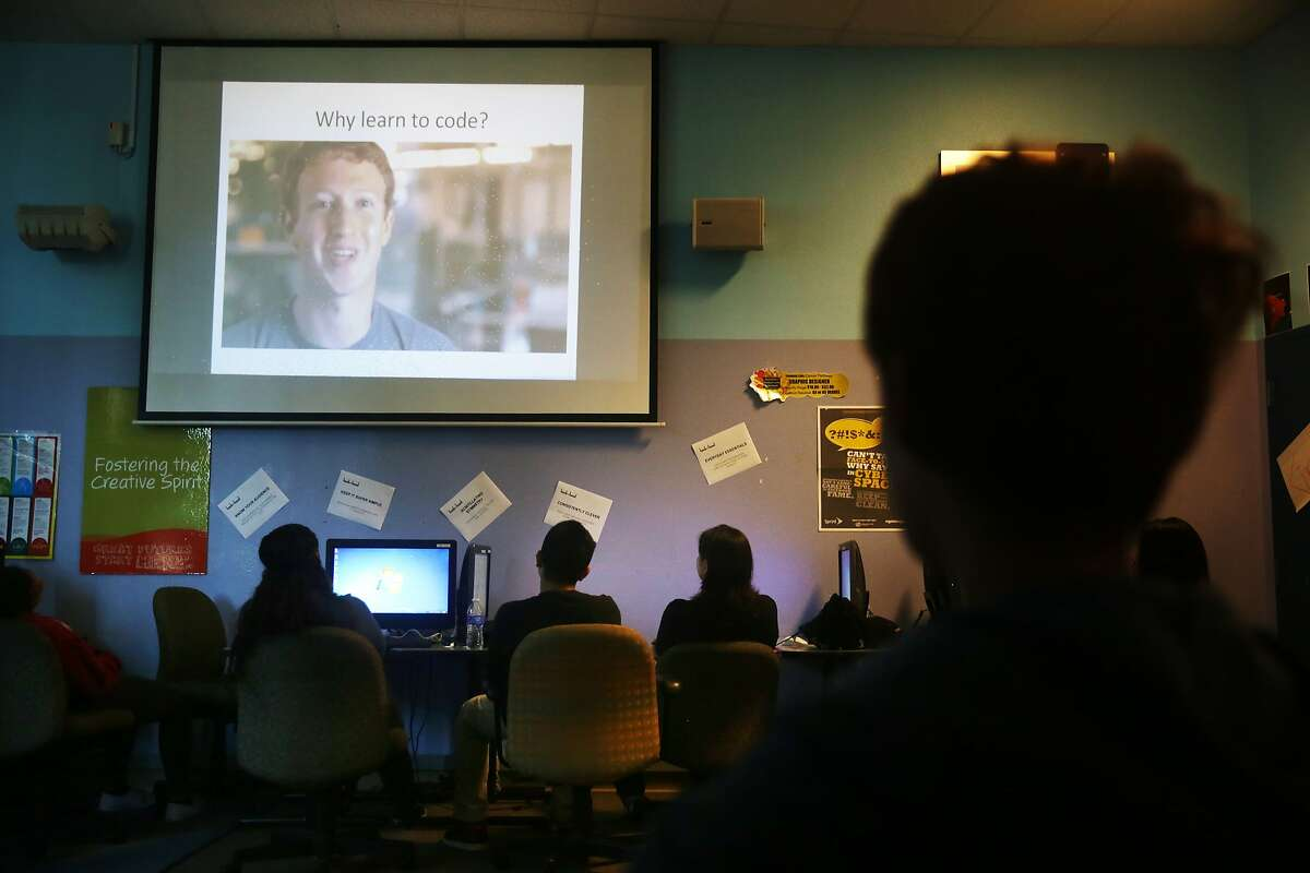 Students in the Hack the Hood Boot Camp listen to Facebook founder Mark Zuckerberg as they watch a video at the start of class on Thursday, June 18, 2015 in East Palo Alto, Calif.
