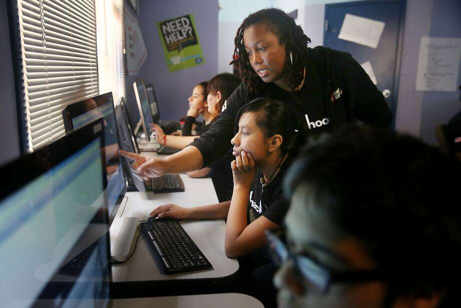 Lyn Muldrow (center standing), program director and lead instructor, gives direction to Jackie Baltierra (center sitting), 16, of Redwood City as students work on their websites during Hack the Hood boot camp  on Thursday, June 18, 2015 in East Palo Alto, Calif. Photo: Lea Suzuki, The Chronicle