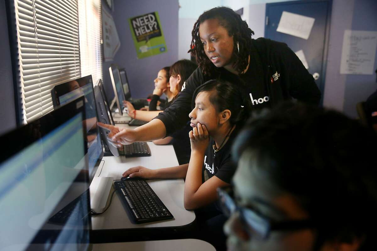 Lyn Muldrow (center standing), program director and lead instructor, gives direction to Jackie Baltierra (center sitting), 16, of Redwood City as students work on their websites during Hack the Hood boot camp on Thursday, June 18, 2015 in East Palo Alto, Calif.