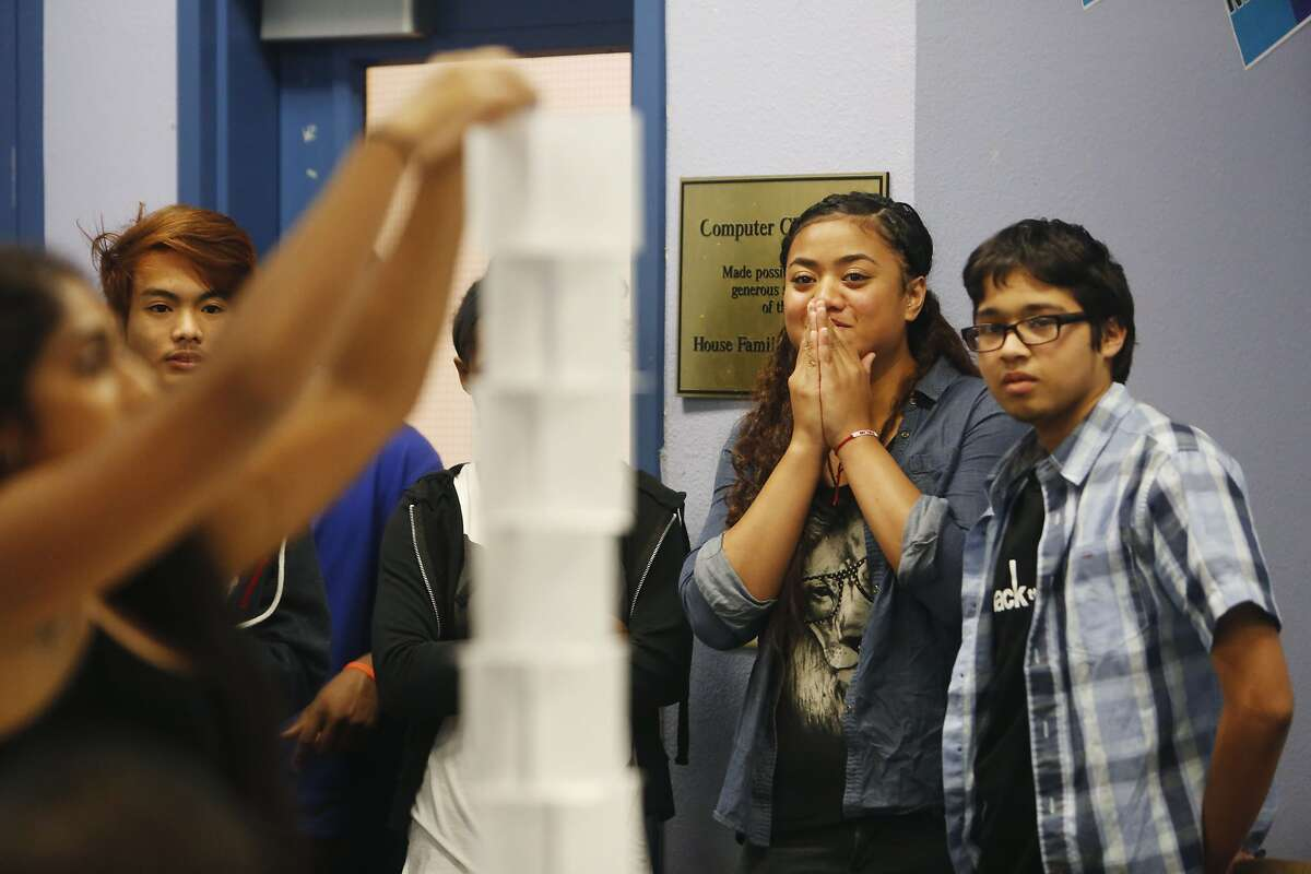 Malia Langi (second from right), 16 of East Palo Alto, watches Saadiqah Hakik (left), 19 ,of East Palo Alto, build a tower out of index cards during a warm up/team building exercise with teammates Mark Francis Daileg (second from left), 17 of East Palo Alto and Pedro Rivera (right), 16 of East Palo Alto during Hack the Hood boot camp on Thursday, June 18, 2015 in East Palo Alto, Calif.