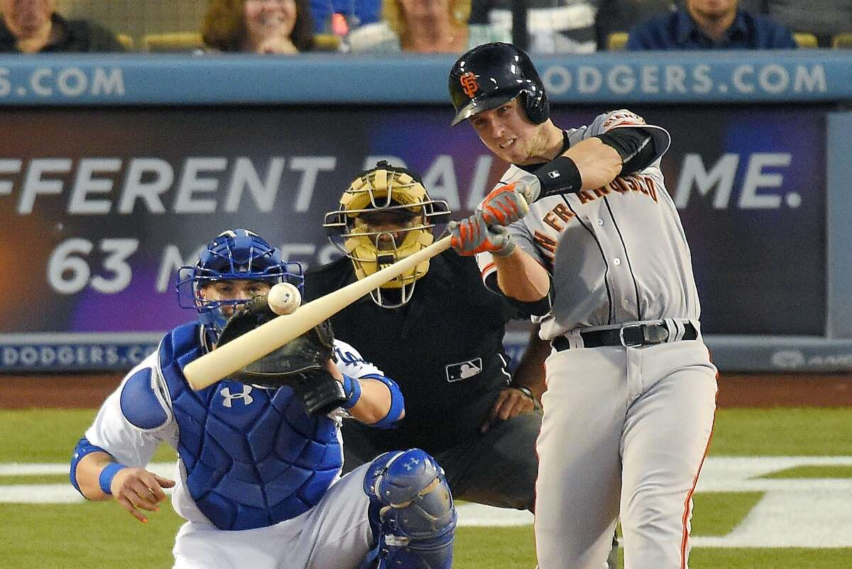 San Francisco Giants' Buster Posey, right, hits a grand slam as Los Angeles Dodgers catcher Yasmani Grandal, left, and home plate umpire Laz Diaz watch during the third inning of a baseball game, Friday, June 19, 2015, in Los Angeles.