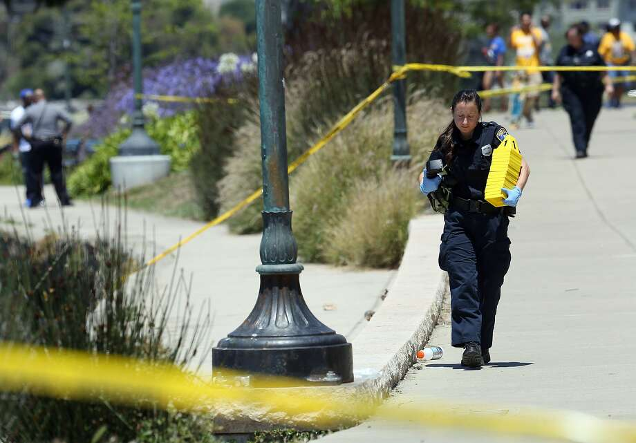 A crime scene technician carries markers as police investigate a shooting on Lakeshore Avenue in Oakland, Calif., on Friday, June 19, 2015. Three people shot five blocks from the NBA championship celebration for the Golden State Warriors in Oakland are in stable condition. Police say they received a call shortly after noon and found three male victims with gunshot wounds.   Photo: Jane Tyska, Associated Press
