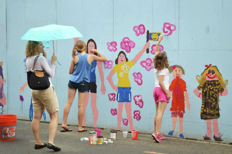 Undeterred by rain, Carine Lauterbach of Westport opened her umbrella as daughters, Sophia, 12, left, and Nina, 9, from continuing work Saturday on the mural on the construction wall surrounding Bedford Square. Photo: Jarret Liotta / For Hearst Connecticut Media / Westport News