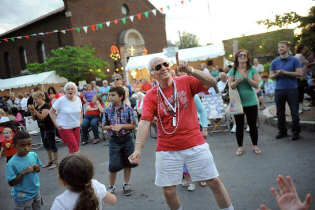 Parishioner Bobby Brignola, center dances to the music during the annual St. Anthony's Festa on Friday, June 19, 2015, at St. Anthony's Church in Schenectady, N.Y. The event continues on Saturday from 3 to 10 p.m. and Sunday from 2 to 9 p.m. (Cindy Schultz / Times Union) Photo: Cindy Schultz / 00032318A