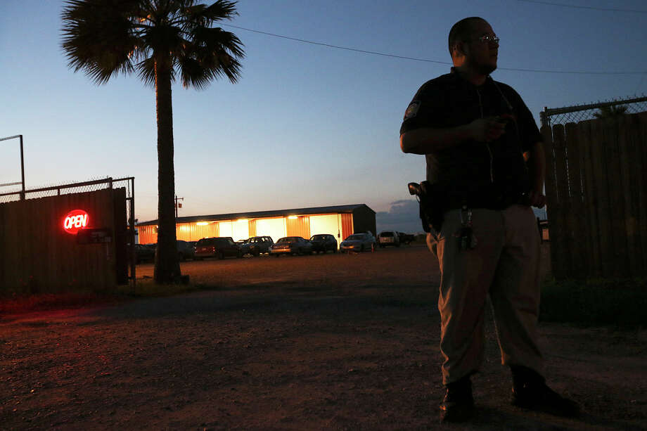 An armed security guard patrols a gambling establishment at the Starr County line near Sullivan City on June 3. Authorities in Hidalgo and Cameron counties, to the south of Starr, have been raiding the business, alleging that they are illegally paying cash prizes. They remove the motherboards from the gambling marchines, known as eight-liners, rendering them useless. Last year, Starr County commissioners approved a $500 permitting fee per slot machine, touting the $1.7 million it would generate for the county. Photo: JERRY LARA /San Antonio Express-News / © 2015 San Antonio Express-News