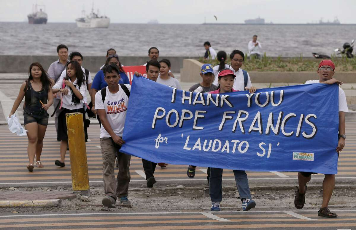"""Environmental activists carry a banner as they march towards a Roman Catholic church to coincide with Pope Francis' encyclical on climate change Thursday, June 18, 2015 in Manila, Philippines. In a high-level, 190-page document released Thursday, Francis describes ongoing human damage to nature as """"one small sign of the ethical, cultural and spiritual crisis of modernity."""" The solution, he says, will require self-sacrifice and a """"bold cultural revolution"""" worldwide. (AP Photo/Bullit Marquez)"""