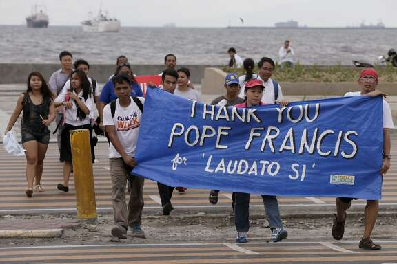 "Environmental activists carry a banner as they march towards a Roman Catholic church to coincide with Pope Francis' encyclical on climate change Thursday, June 18, 2015 in Manila, Philippines. In a high-level, 190-page document released Thursday, Francis describes ongoing human damage to nature as ""one small sign of the ethical, cultural and spiritual crisis of modernity."" The solution, he says, will require self-sacrifice and a ""bold cultural revolution"" worldwide. (AP Photo/Bullit Marquez)"