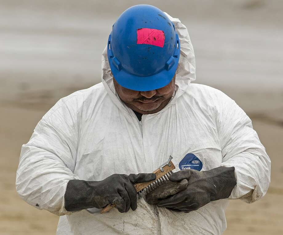A hand crew member scraps oil residues from a small rock from areas affected by an oil spill at Refugio State Beach, north of Goleta, Calif., on Wednesday, June 10, 2015. The May 19 spill occurred after an onshore pipeline operated by Texas-based Plains All American ruptured. (AP Photo/Damian Dovarganes) Photo: Damian Dovarganes, Associated Press