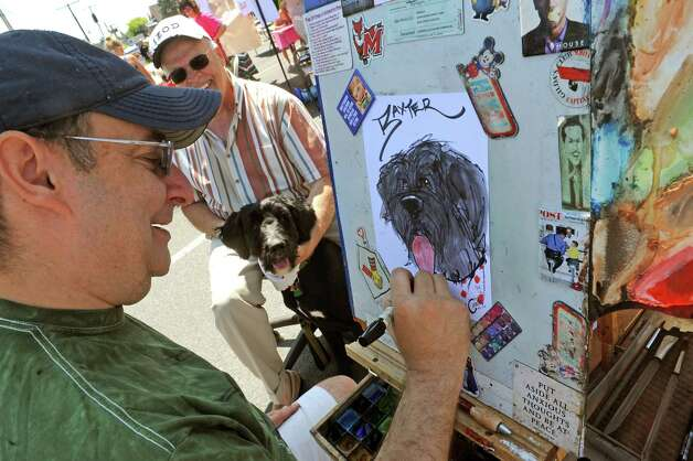 Artist Rich Conley does a caricature of dog Baxter as his owner Ed Wildzunas sits with him during the Upper Union Street Strawberry Fest & Art Show on Saturday June 20, 2015 in Schenectady, N.Y.  (Michael P. Farrell/Times Union) Photo: Michael P. Farrell / 00032312A