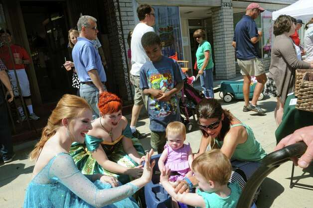 Amy Buhrmaster, left, dresses as Queen Elsa high fives two-year-old Nora Grove during the Upper Union Street Strawberry Fest & Art Show on Saturday June 20, 2015 in Schenectady, N.Y.  (Michael P. Farrell/Times Union) Photo: Michael P. Farrell / 00032312A