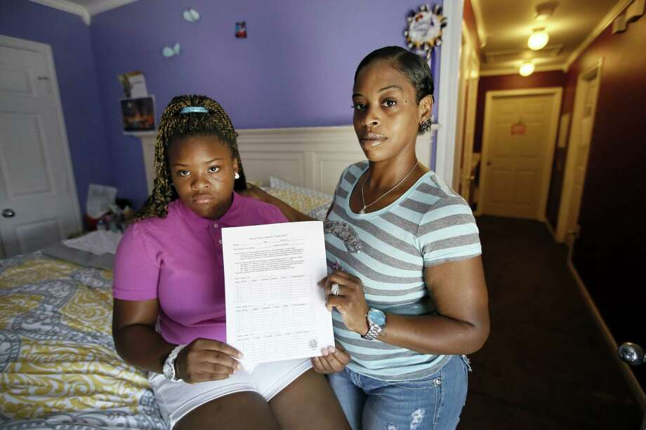 Natod'Ja Washington, left, 16, poses for a photo with her mother Natasha Holloway in their home as they hold a student sign in sheet for truancy court Friday, June 19, 2015, in Dallas. The form must be signed by all of her teachers confirming Washington's attendance in school. (AP Photo/Tony Gutierrez) Photo: Tony Gutierrez, STF / Associated Press / AP