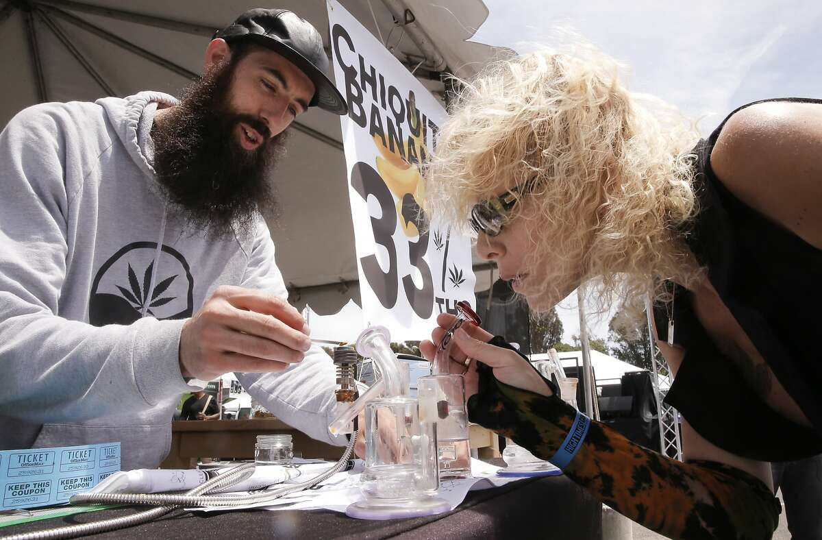 Jesse Bower with, @utopia Farms helps Char Gamble of Humbolt County sample their product as vendors gathered for Cannabis Cup, the world's largest marijuana trade show taking place at the Cow Palace in San Francisco, Calif. on Sat. June 20, 2015.