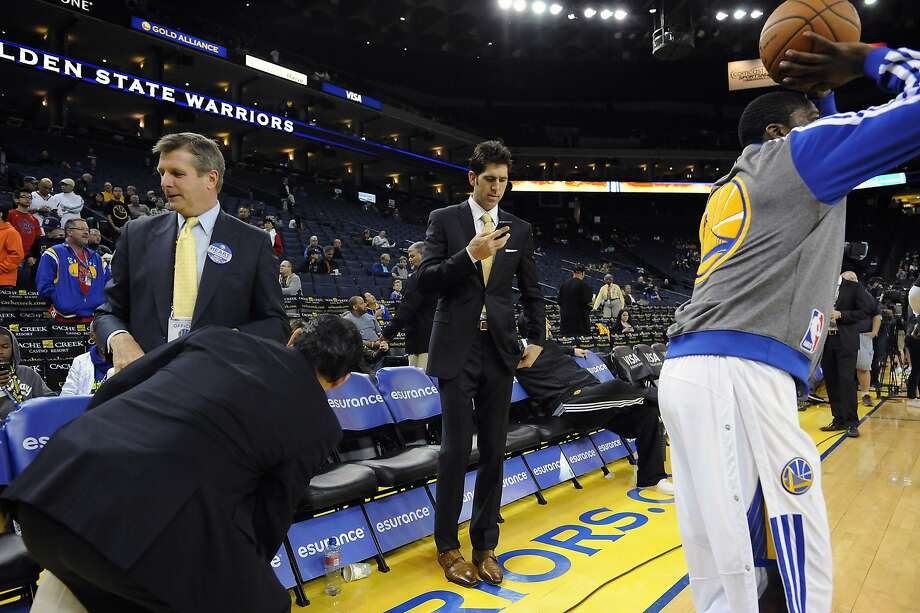 Golden State Warriors general manager Bob Myers checks his phone as players warm up before their game against the Brooklyn Nets at Oracle Arena in Oakland, CA Saturday, February 22, 2014. Photo: Michael Short, Special To The Chronicle