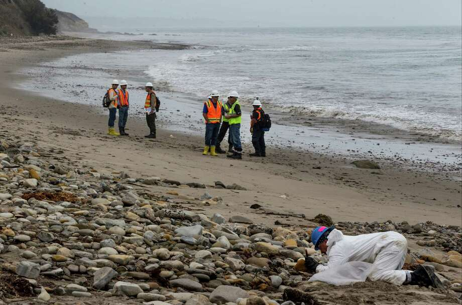 Shoreline Cleanup Assessment Technique team members, left, evaluate oil coverage as a hand crew worker scraps areas affected by an oil spill at Refugio State Beach, north of Goleta, Calif., on Wednesday, June 10, 2015. The May 19 spill occurred after an onshore pipeline operated by Texas-based Plains All American ruptured. (AP Photo/Damian Dovarganes) Photo: Damian Dovarganes, STF / AP